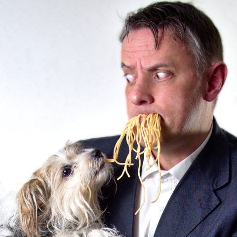louie the entertainer eating spaghetti with his dog