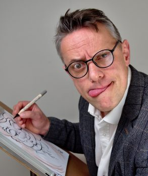 a silly man wearing glasses drawing a caricature at a wedding